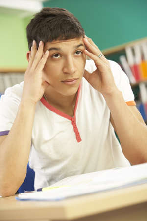 non uniform: Stressed Male Teenage Student Studying In Classroom