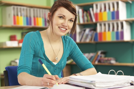 student desk: Teenage Female Student In Working In Classroom