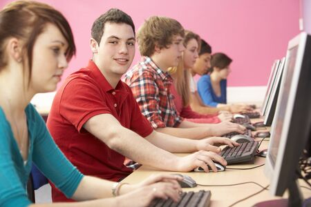 student desk: Teenage Students In IT Class Using Computers In Classroom Stock Photo