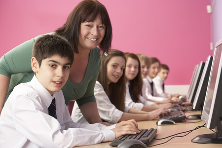 Teenage Students In IT Class Using Computers In Classroom With Tutor photo