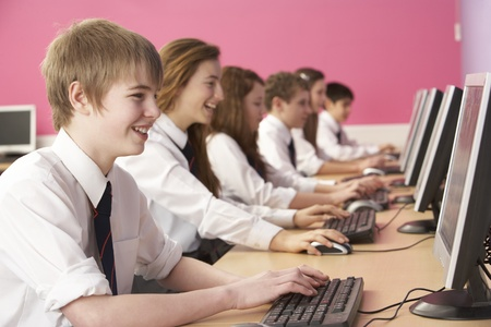 uniform student: Teenage Students In IT Class Using Computers In Classroom Stock Photo