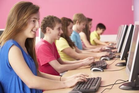 education technology: Teenage Students In IT Class Using Computers In Classroom Stock Photo