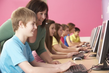 non uniform: Teenage Students In IT Class Using Computers In Classroom With Tutor