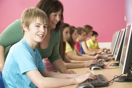 middle class: Estudiantes adolescentes en la misma clase utilizando ordenadores en aulas con Tutor