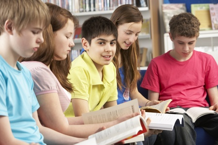 learning to read: Teenage Students In Library Reading Books Stock Photo