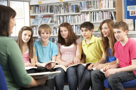 tutorial: Teenage Students In Library Reading Books With Tutor Stock Photo