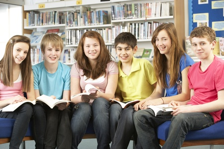 non uniform: Teenage Students In Library Reading Books Stock Photo