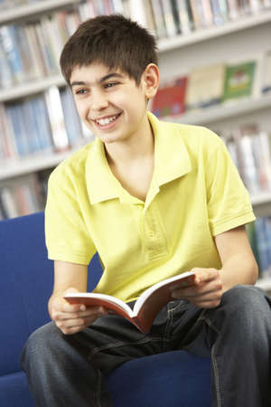 non uniform: Male Teenage Student In Library Reading Book
