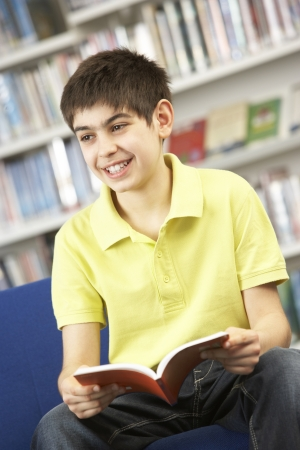 Male Teenage Student In Library Reading Book photo