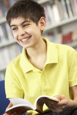 Male Teenage Student In Library Reading Book Stock Photo - 9912027
