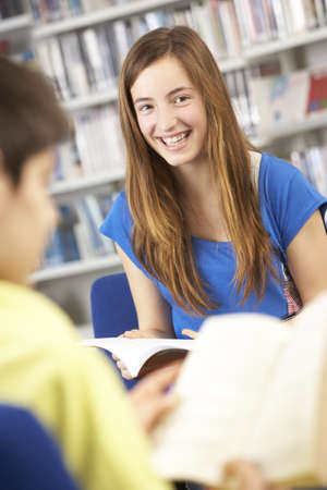 Female Teenage Student In Library Reading Book photo