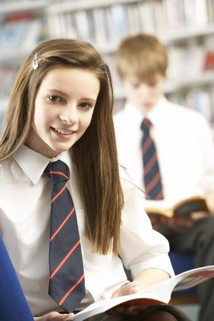 Female Teenage Student In Library Reading Book Stock Photo - 9911062