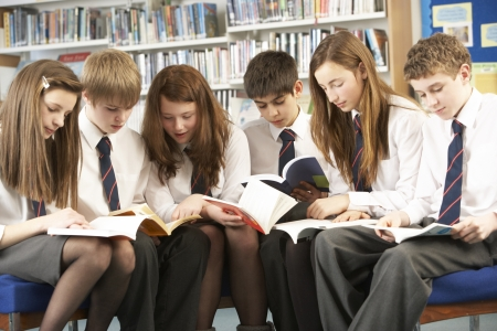 secondary school: Teenage Students In Library Reading Books Stock Photo