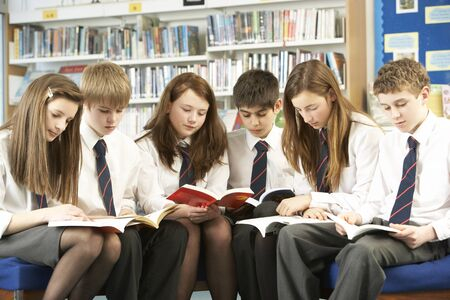 school children uniform: Teenage Students In Library Reading Books Stock Photo