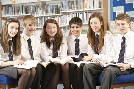 uniform student: Teenage Students In Library Reading Books Stock Photo