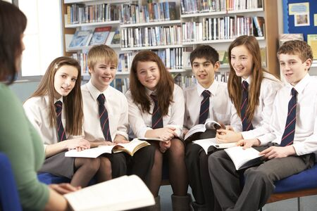 school aged: Teenage Students In Library Reading Books With Tutor Stock Photo