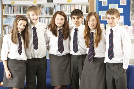 uniforme: Retrato de grupo de estudiantes adolescentes en biblioteca