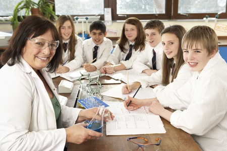 experiment: Group Of Teenage Students In Science Class With Tutor Stock Photo