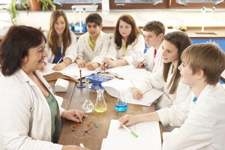 experimento: Grupo de estudiantes adolescentes en clase de Ciencias con Tutor Foto de archivo