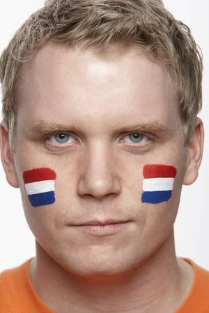 Young Male Sports Fan With Dutch Flag Painted On Face photo