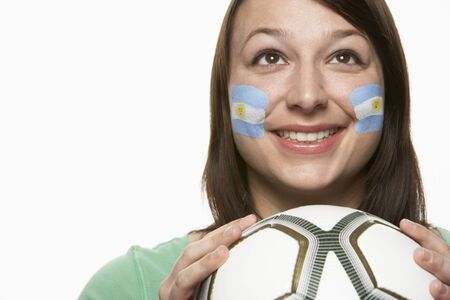 Young Female Football Fan With Argentinian Flag Painted On Face photo