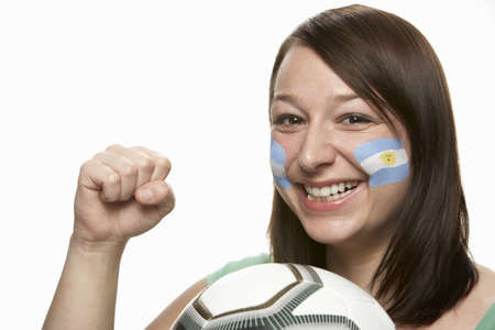 argentinian flag: Young Female Football Fan With Argentinian Flag Painted On Face