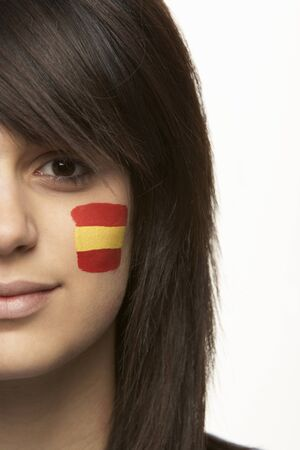 Young Female Sports Fan With Spanish Flag Painted On Face photo