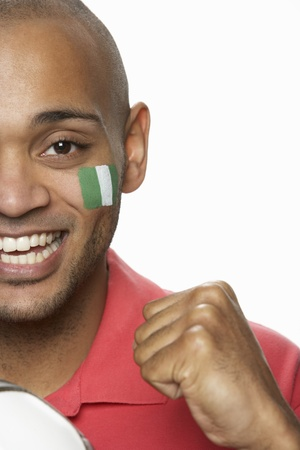 Young Male Football Fan With Nigerian Flag Painted On Face photo