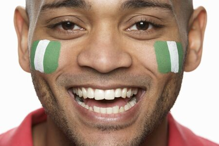 Young Male Sports Fan With Nigerian Flag Painted On Face photo