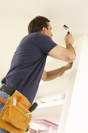 Electrician Installing Light Fitting In Home photo