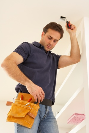 fitting: Electrician Installing Light Fitting In Home