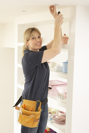 fitting in: Female Electrician Installing Light Fitting In Home