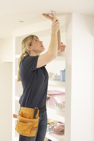 Female Electrician Installing Light Fitting In Home photo