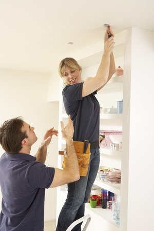 Electrician Teaching Apprentice To Install Light Fitting In Home photo