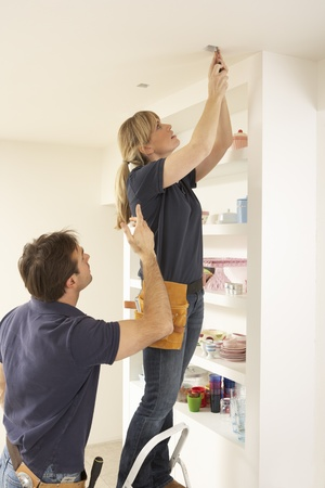 fitting in: Electrician Teaching Apprentice To Install Light Fitting In Home