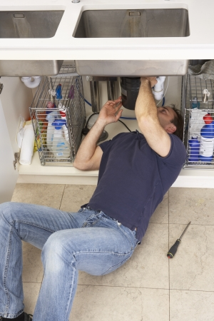 Plumber Working On Sink In Kitchen Stock Photo - 9911270