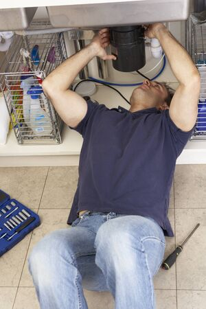 Plumber Working On Sink In Kitchen Stock Photo - 9911401