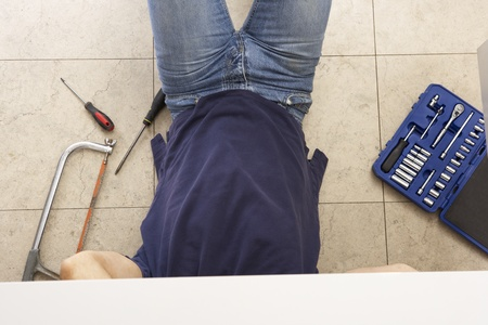 Plumber Working On Sink In Kitchen Stock Photo - 9911136