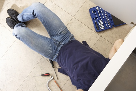 Plumber Working On Sink In Kitchen Stock Photo - 9908347