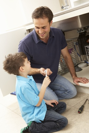 Son Helping Father To Mend Sink In Kitchen Stock Photo - 9911327