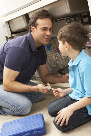 Son Helping Father To Mend Sink In Kitchen Stock Photo - 9911238