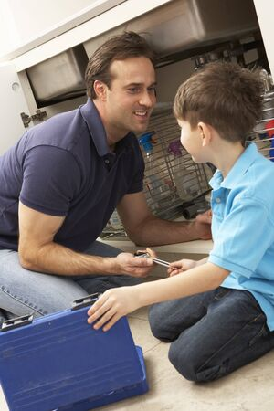 Son Helping Father To Mend Sink In Kitchen Stock Photo - 9911376