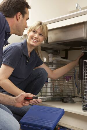 Plumber Teaching Apprentice To Fix Kitchen Sink In Home photo