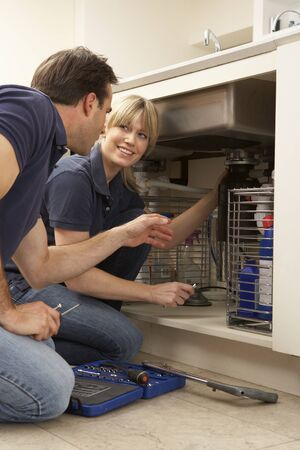 Plumber Teaching Apprentice To Fix Kitchen Sink In Home Stock Photo - 9911483