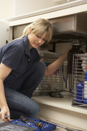 Female Plumber Working On Sink In Kitchen Stock Photo - 9911283