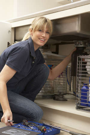 Female Plumber Working On Sink In Kitchen Stock Photo - 9911300