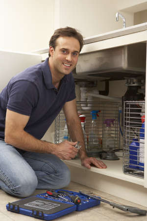 Plumber Working On Sink In Kitchen Stock Photo - 9911398