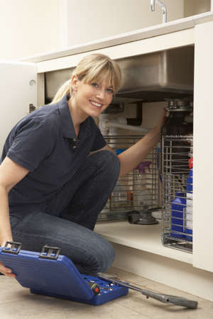 Female Plumber Working On Sink In Kitchen Stock Photo - 9908862
