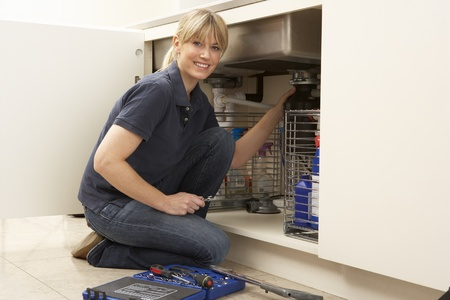 Female Plumber Working On Sink In Kitchen Stock Photo - 9911663