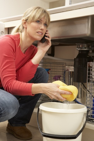 Woman Mopping Up Leaking Sink On Phone To Plumber Stock Photo - 9911396